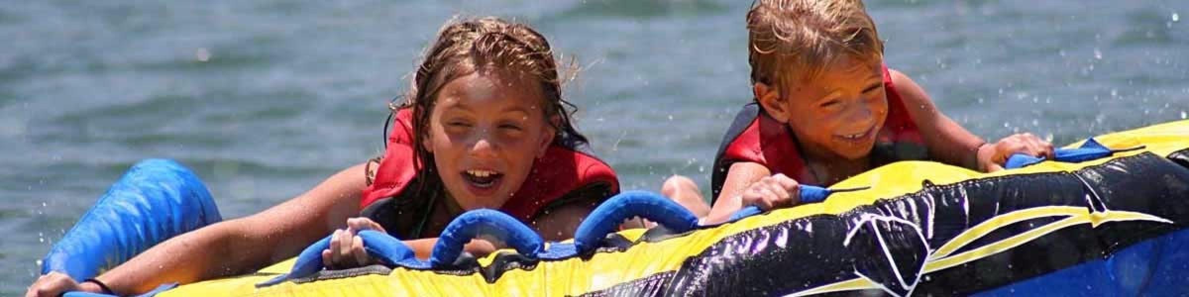 2015-kids-tubing-on-lake-having-fun-slider